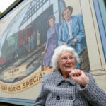 Mary McArthur in front of her picture on the I C ART Cheshire Lines artwork created by artist Rachelle