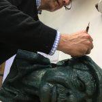 Original artist, Simon Law calving his signature into the moulded head